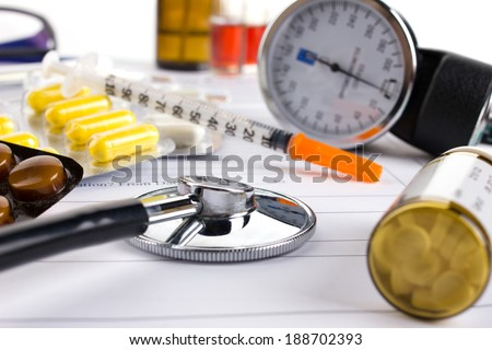 stethoscope, insulin syringe and different medicament on medical form - stock photo