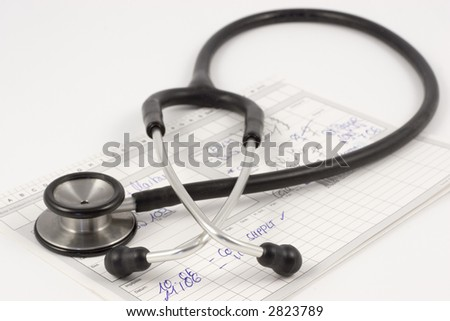 Stethoscope lying on a medical report on a white desk - stock photo