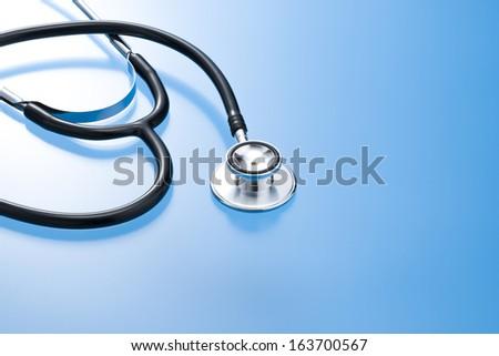 Stethoscope of medical on blue background - stock photo
