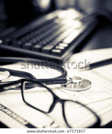 Stethoscope on a prescription form with glasses pen and keyboard, very shallow DOF - stock photo