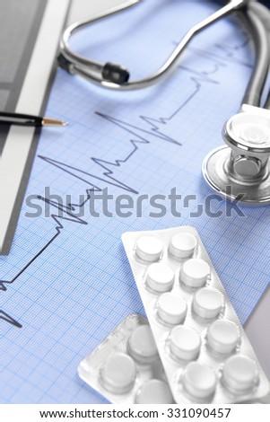 Stethoscope on cardiogram  sheet, closeup - stock photo
