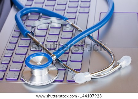 stethoscope on laptop keyboard - modern medicine concept - stock photo
