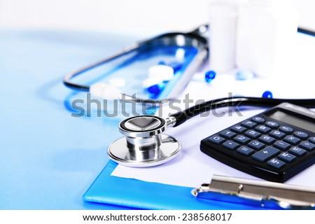 Stethoscope on light blue background - stock photo