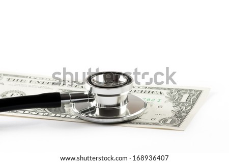 stethoscope on one dollar under white background with space for text, cost of medical health care - stock photo