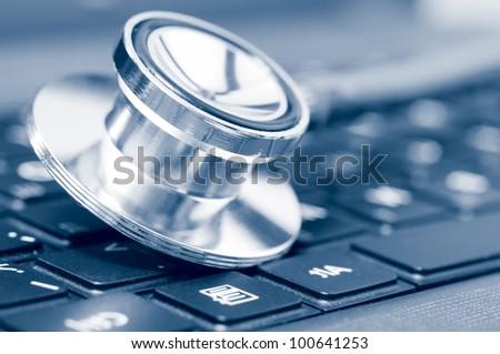 stethoscope on the laptop keyboard, blue toned - stock photo