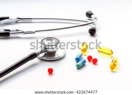 stethoscope on white background with mix pills isolated - stock photo