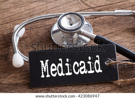 Stethoscope on wood with Medicaid words as medical concept - stock photo
