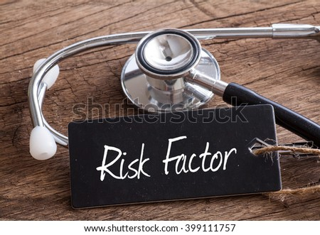 Stethoscope on wood with Risk factor words as medical concept - stock photo