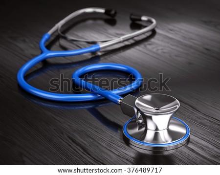 Stethoscope on wooden background - stock photo