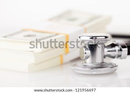 stethoscope placing on US dollar banknotes on white background - stock photo