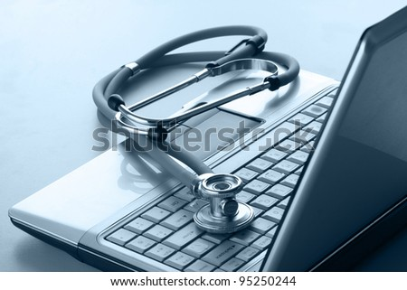 Stethoscope resting on a computer keyboard - stock photo
