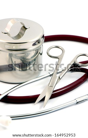 Stethoscope, surgical scissors and sterile jar in the emergency room. - stock photo