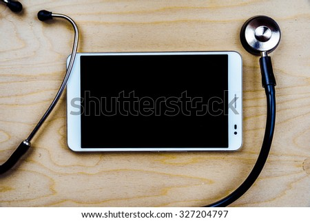 Stethoscope with a tablet computer on wooden table. Medical background - stock photo