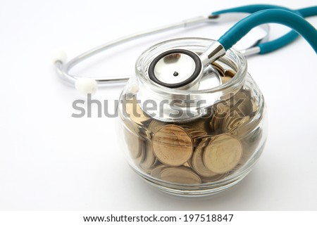 stethoscope with coins in the savings, financial concept - stock photo
