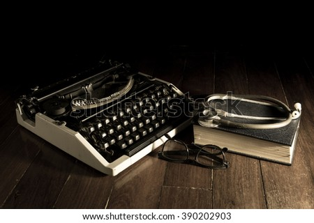 Stethoscope with eyeglasses book and typewriter. - stock photo