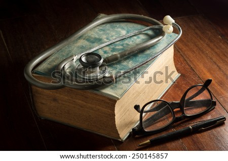 Stethoscope with eyeglasses,pen and antique book. - stock photo
