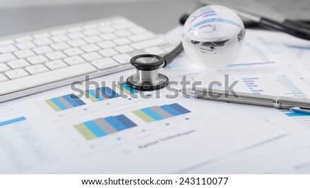 Stethoscope with financial on the desk. - stock photo