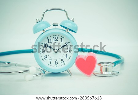 Stethoscope with heart and alarm clock. - stock photo