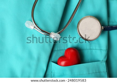 Stethoscope with heart on suit background, close-up - stock photo