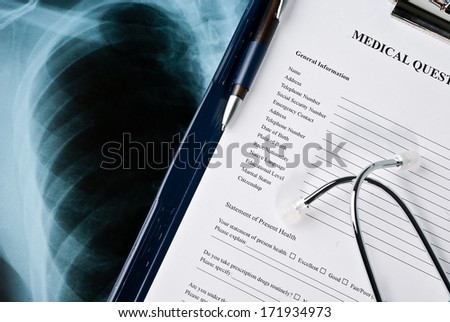 Stethoscope with medical ID tag on medical document (medical questionnaire) and Xray photo of lungs - stock photo