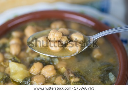 Stew of chickpeas and spinach with cod on a  table with a tablecloth - stock photo