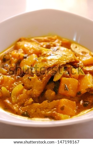 Stew seitan with yellow peppers and spices in white dish - stock photo