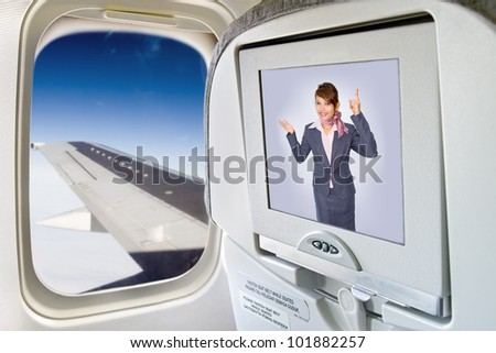 Stewardess informed of the display on the aircraft seat. Monitor and a window on the plane. Air hostess on television in flying aircraft. The screen with flight crew next window with aircraft's wing. - stock photo
