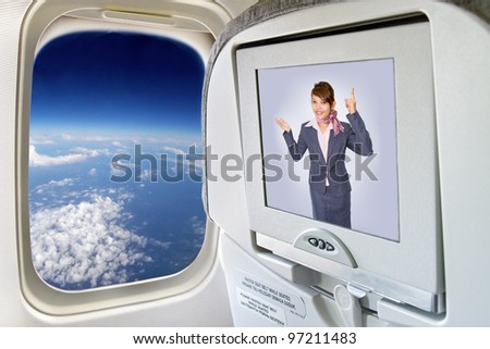 Stewardess on the plane on monitor. Information from Air hostess in display plane flying over the world. Screen television in plane next to window overlooking the globe. Aircraft flies over the Earth. - stock photo
