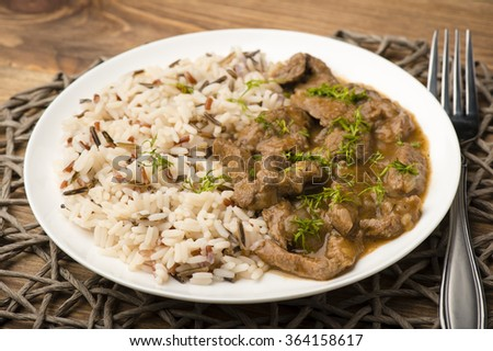 Stewed beef and rice on the white plate on wooden background. - stock photo
