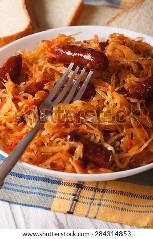 stewed cabbage with sausages close-up in white plate. vertical - stock photo