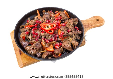 Stewed chicken livers with paprika and pomegranate seeds in cast iron pan. Isolated on a white background. - stock photo