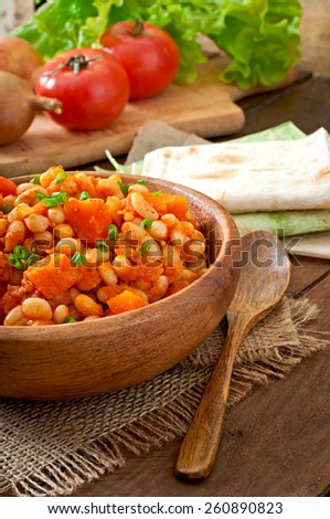 Stewed white beans and sliced pumpkin in tomato sauce - stock photo