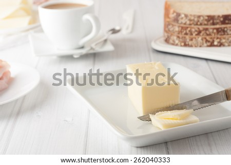 stick of butter on white plate with coffee and bread at the background - stock photo