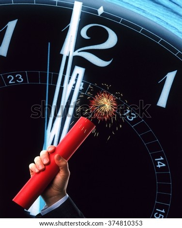 Stick of dynamite in his hand on the background of the dial - stock photo