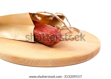 Stick sausage in a paper bag on a wooden cutting board isolated on a white background. - stock photo