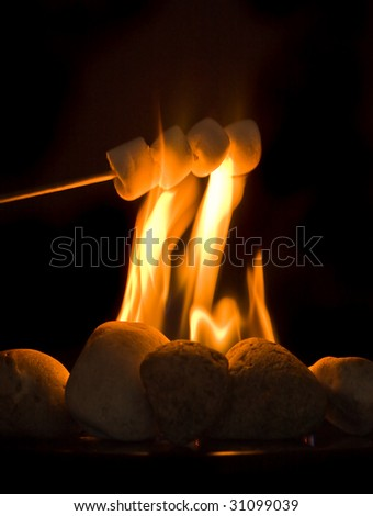 Stick with four marshmallows held above burning fire - stock photo
