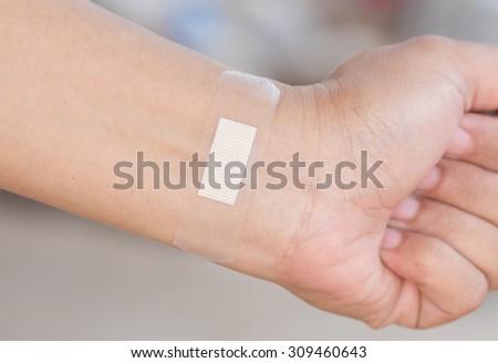 Sticking plaster on the wrist. - stock photo