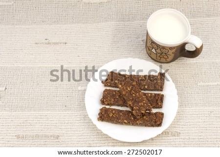 Sticks of oatmeal with chocolate, healthy breakfast with milk - stock photo