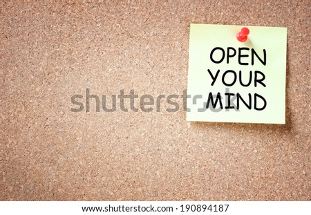 sticky note over cork board with the phrase open your mind. room for text. - stock photo