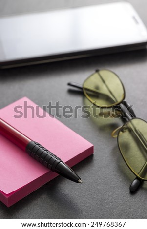 Sticky note, pen and  glasses on table, close up - stock photo