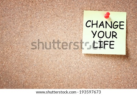 sticky note pinned to board with the phrase change your life - stock photo