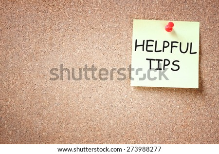 sticky note pinned to cork board with the phrase helpful tips written on it room for text - stock photo