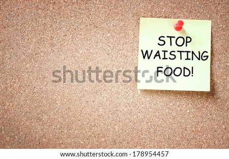 sticky note pinned to corkboard with the phrase stop waisting food - stock photo