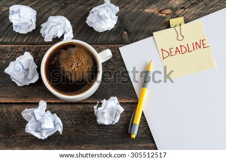 Sticky note with the word deadline. White blank paper, crumpled paper, pen and a cup of coffee on a wooden background - stock photo