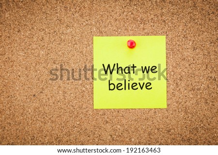 sticky note with word what we believe on corkboard, business concept - stock photo