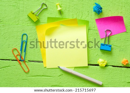 Sticky notes isolated on wooden background with clipping path pins and other office supplies . Above view - stock photo