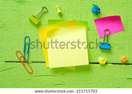 Sticky notes isolated on wooden background with clipping path pins and other office supplies . Above view. - stock photo