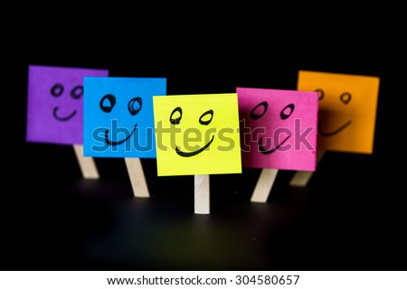 sticky notes with happy faces isolated on a black background for a happy team concept - stock photo