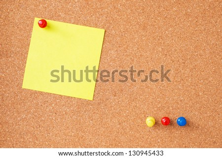Sticky notes with thumbtacks on cork board - stock photo