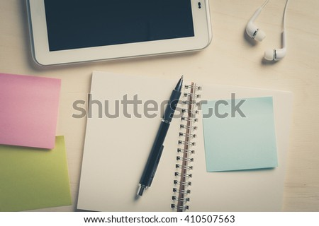 Sticky paper with blank area for text or message, opened notebook,and pen beside small tablet pc and in ear headset on wood table with vintage filter effect - stock photo
